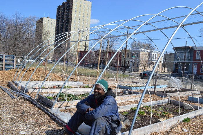 Devon Bailey, a PUC, sits by the hoop house.